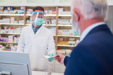 Professional pharmacist with protective mask and face shield on his face  working with customer in...