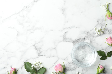 Flat lay composition with cosmetic gel and beautiful flowers on white marble table. Space for text