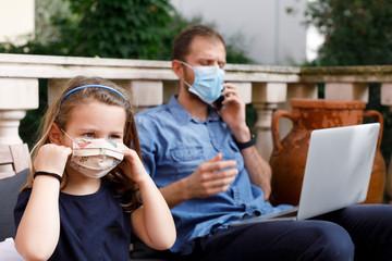 bambina vicino al papa che lavora al computer e fa un a telefonata in modalità smart working ,...