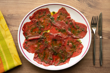 Beef carpaccio with basil marinade on wooden background