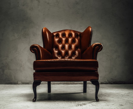 Luxorious brown leather vintage armchair standing in a dark studio