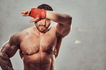 Shirtless bodybuilder showing his muscles while posing in a studio and covering his eyes from sun