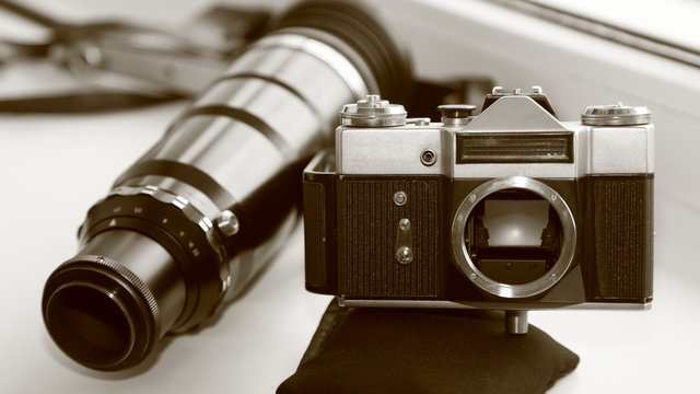 Professional vintage 35 mm film camera with a large 300 mm telephoto lens on white background close up