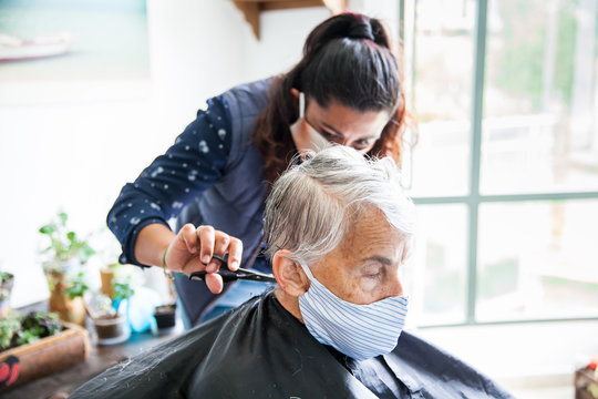 Senior woman getting a haircut at home during Covid-19 pandemic wearing face mask