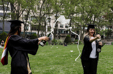 Molloy College Nursing School graduates Taylor Laufer and Yuliya Dubyna make a toast in Bryant Park in New York