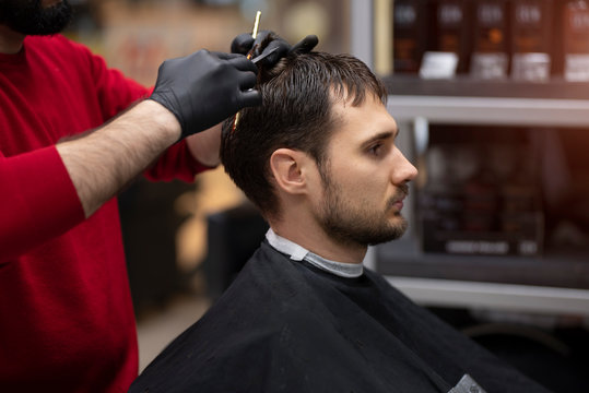A young man in a Barber shop. Trendy guy with dark hair.