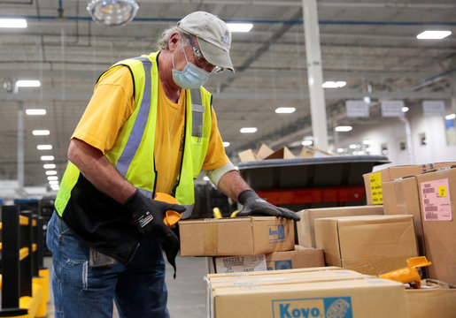 Dana Inc. assembly technician Mark Popovich wears a face mask as he opens supplies boxes to assemble axles for automakers, amid the coronavirus (COVID-19) outbreak, in Toledo