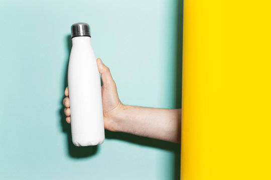 Close-up of male hand holding steel reusable thermo water bottle of white with mockup, between two backgrounds of yellow and aqua menthe colors.