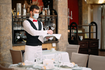 A waiter in a medical protective mask serves the table in the restaurant.