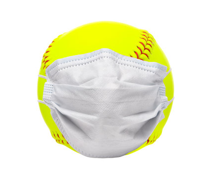 Sports and Covid-19-Concept. Yellow softball with a surgical mask on white background.