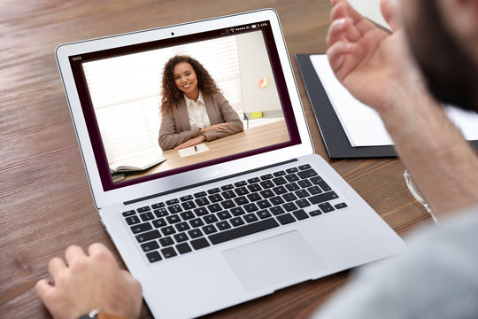 Man using video chat for online job interview in office, closeup