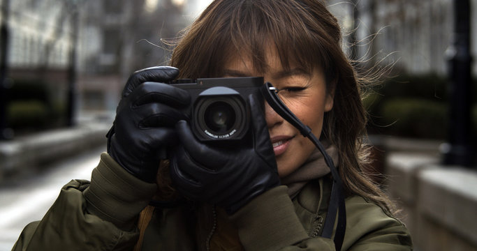 Street photographer focuses her camera while taking a photograph of her subject