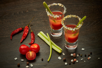 Two shot glasses with cocktail Bloody Mary on dark wooden background