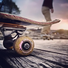 Close-up Of Skateboard With Blurred Man Skateboarding Behind