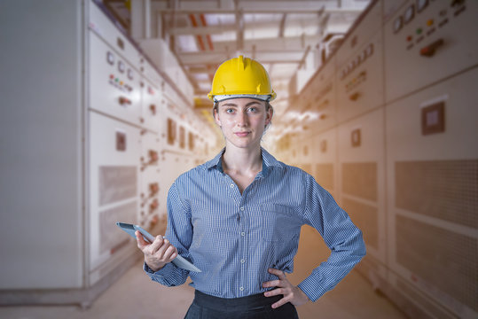 Young strong women engineer working for checking and monitoring status high voltage vacuum DC circuit breaker switch gear electrical distribution substation in program high technology on tablet