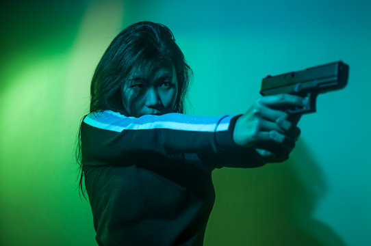 cinematic portrait of young attractive and dangerous special agent woman spy or Asian Korean mobster girl holding handgun pointing the gun fierce in Hollywood style