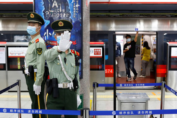 A Paramilitary police officers gestures at the photographer while keeping watch at a station of Line 1 of the metro that runs past the Great Hall of the People