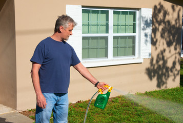 Homeowner man spraying weed killer on the grass on grass in his yard with hose attachment full of chemicals