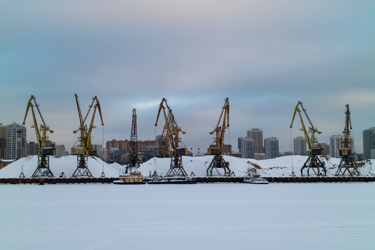 The image of the port cranes at the frozen river.
