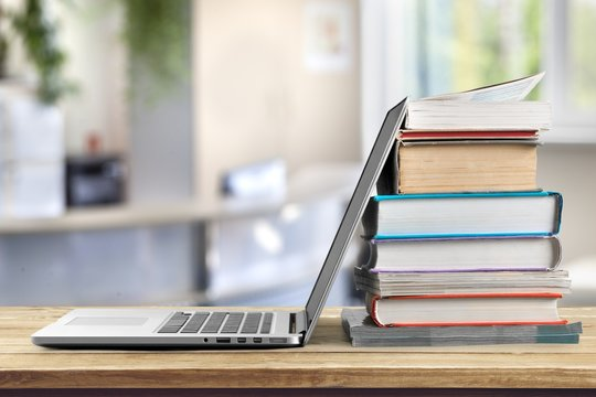 Stack of books with a modern laptop on the table