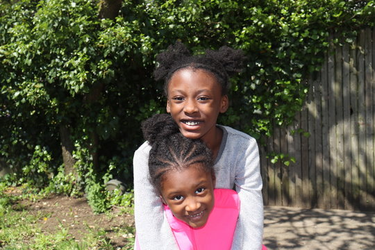Black Children smiling while posing outside with bushes in background