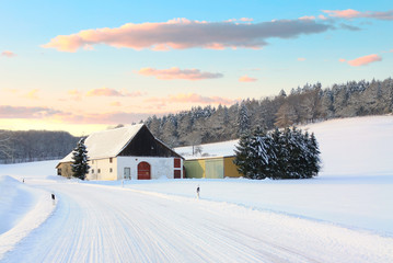 A snowy winter landscape in East Westphalia in Germany. In the middle a farmhouse and in the background a fir forest. In the foreground is a curve with a white, snow-covered road.