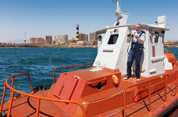 A pilot boat on the Mediterranean Sea in front of the Faro del Estacio lighthouse near the port city of Torrevieja. The bearded captain stands on the deck with binoculars in his hand.