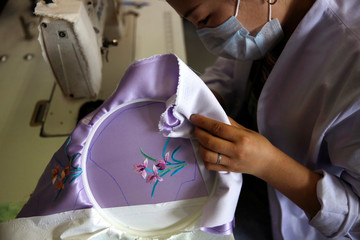 Worker wearing a face mask embroiders a flower pattern on a silk cloth for making a face mask designed by Zhou Li,