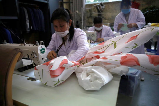 Worker wearing a face mask sews PPE cloth to make a protective suit designed by Zhou Li, at a studio in Beijing
