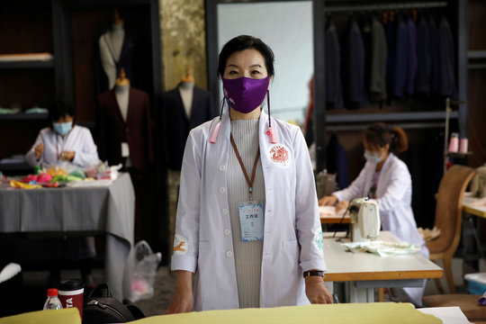 Fashion Designer Zhou Li wearing her designed silk face mask poses for pictures, at a studio in Beijing