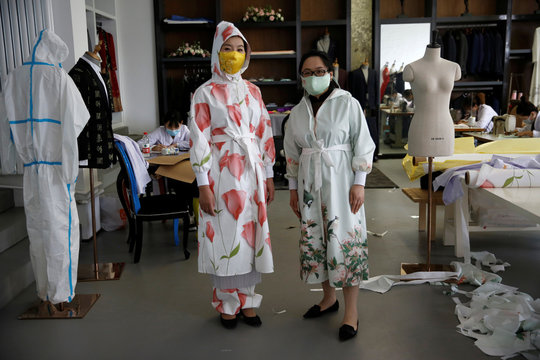 Designer Zhou Li and Ni Zan'er in protective suits and silk face masks designed by Zhou, pose for pictures at a studio in Beijing