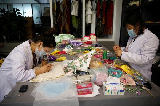 Workers wearing face masks make silk face masks designed by Zhou Li, at a studio in Beijing