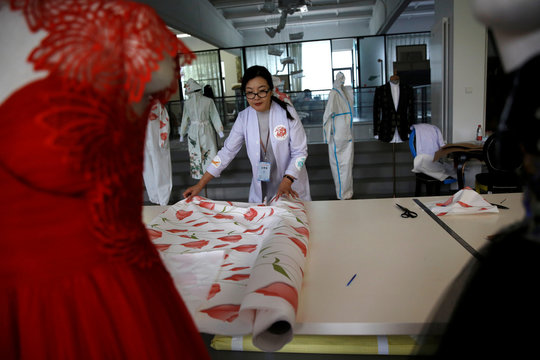 Designer Zhou Li spreads out PPE cloth used for making her designed protective suits, at a studio in Beijing