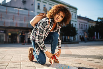 Young attractive female tourist with curly hair crouching at square and tying shoelace.