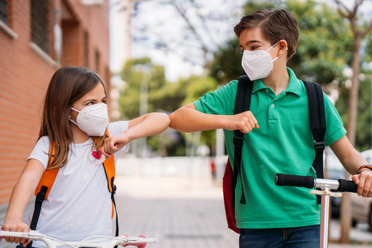 Boy and girl with mask greeting on the street during the coronavirus pandemic