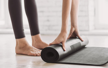 Female hands rolling up exercise mat and preparing doing yoga. Young woman meditating at home. Girl practicing yoga in class. Relaxation, body care, healthy lifestyle, exercising, training concept