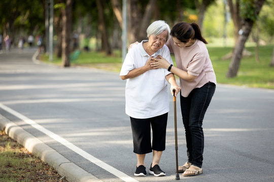 Old elderly with short of breath and chest pain from heart disease, heart attack or heart failure while walking to exercise in outdoor at the park,senior woman with illness,symptoms of dyspnea,angina.