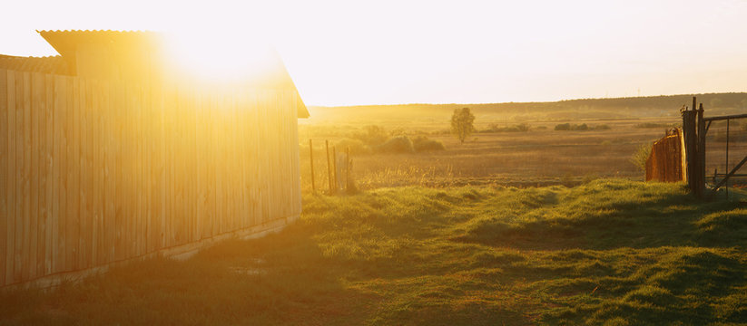 Rural landscape. The sun breaks through the barn. Green and Golden grass on a spring evening. | KOROVYAKOVA, SVERDLOVSKAYA OBLAST - 9 MAY 2020.