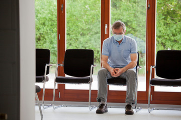 Mature patient or visitor sitting alone in an empty waiting room of an office or hospital