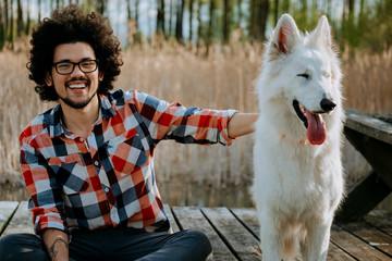 Smiley man and a dog companion sitting on a bridge at a lake
