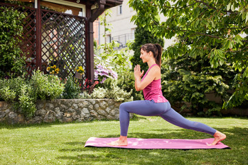 Side view of attractive fit yogi brunette standing in backyard on mat in Crescent Lunge with Prayer Hands yoga posture.