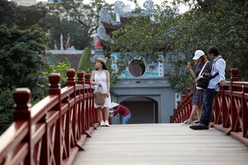 Vietnamese tourists pose for photos on the The Huc bridge at Hoan Kiem lake after the Vietnamese government eased the lockdown following the coronavirus disease (COVID-19) outbreak, in Hanoi