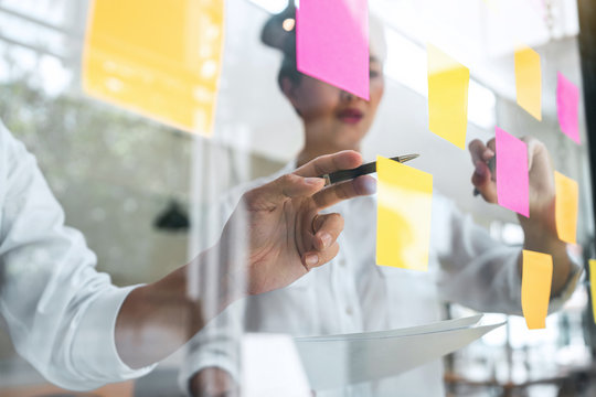 Young creative team professional using post it notes in glass wall to writing strategy business plan to development grow to success