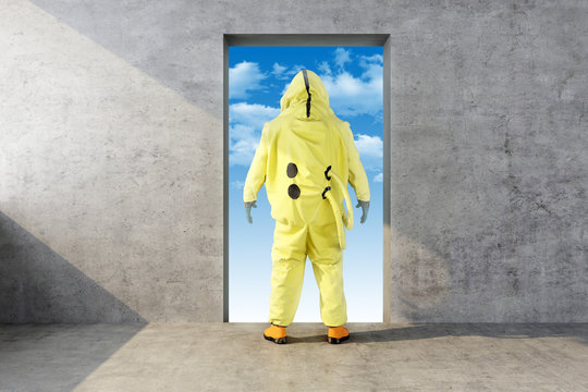 man in yellow chemical protective suit looks in the opening in the wall with the sky