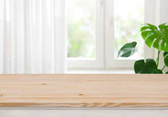 Wooden table top for product display over blurred curtained window