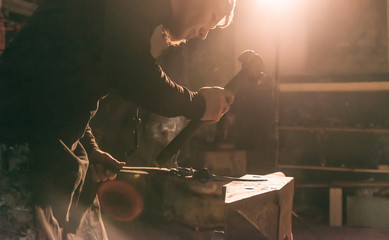 Blacksmith forging metal on the anvil.