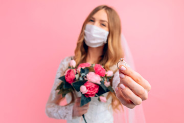 A bride in a wedding dress and a medical protective mask on her face on a pink background. Wedding,...