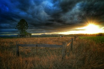 Fence On Field Against Dramatic Sunset Sky - fototapety na wymiar