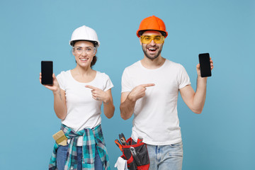 Funny couple woman man in hardhat glasses point index finger on mobile phone with blank empty...