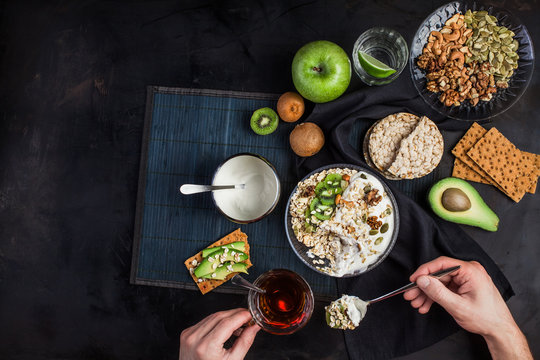 The man is eating porridge. A healthy breakfast all day long. A bowl with cereals, nuts and yogurt. Bread with avocado. Glass of water on a dark background. Useful food 24 hours.